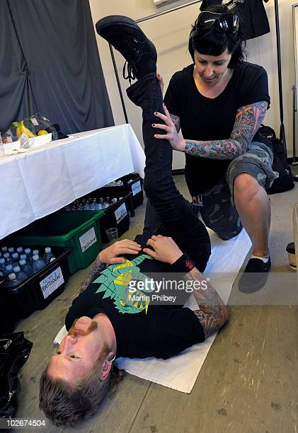 Bill Kelliher of Mastodon stretches with a tattooed physiotherapist prior to performing on stage at the Big Day Out at Flemington Race Course on...
