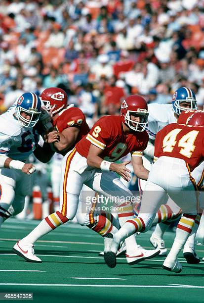 Bill Kenney of the Kansas City Chiefs turns to hand the ball off to Herman Heard against the Denver Broncos during an NFL football game October 27...