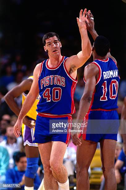 Bill Laimbeer and Dennis Rodman of the Detroit Pistons high five against the Los Angeles Lakers during a game at the Great Western Forum in Inglewood...