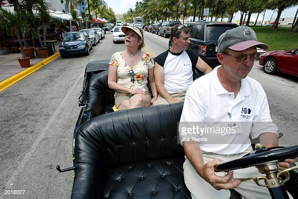 Bill Leland from Farmington Hills Michigan drives a Model T Ford while Barbara Cadmus from Rockaway New Jersey and Dean Baer from New Providence New...