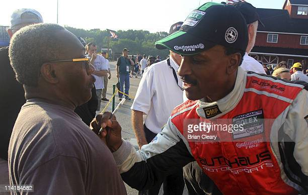 Bill Lester signs an autograph for a fan after winning the GT claas in the Bosch Engineering 250 at Virginia International Raceway on May 14 2011 in...