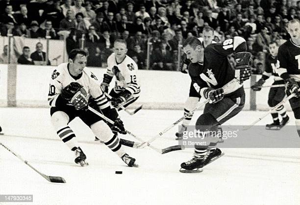 Bill Masterton of the Minnesota North Stars skates with the puck as Dennis Hull of the Chicago Blackhawks defends on March 17 1968 at the Met Center...