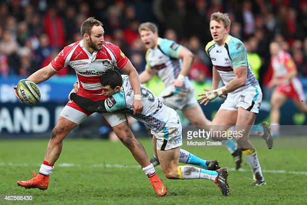 Bill Meakes of Gloucester looks for support as Tom Habberfield of Ospreys holds on during the LV=Cup match between Gloucester Rugby and Ospreys at...