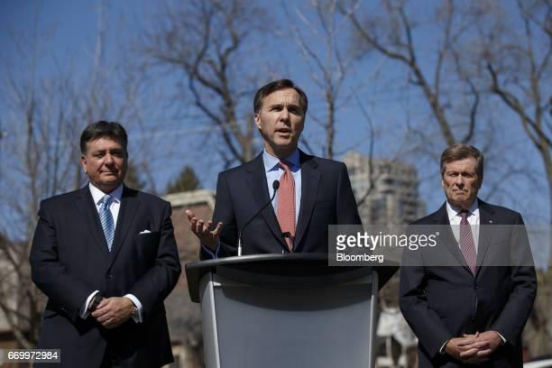 Bill Morneau, Canada's finance minister, center, speaks while Charles Sousa, Ontario's finance minister, left, and John Tory, mayor of Toronto,...