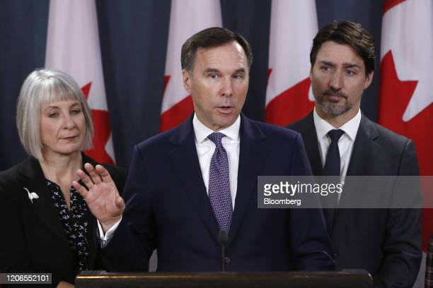 Bill Morneau Canada's finance minister center speaks while Patty Hajdu Canada's health minister left and Justin Trudeau Canada's prime minister...
