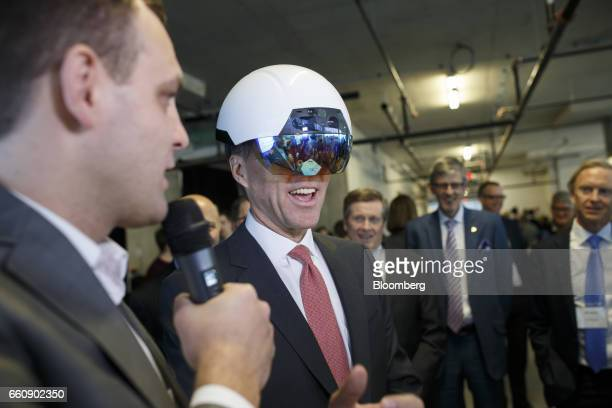 Bill Morneau Canada's finance minister center tries on a virtual reality helmet during an artificial intelligence demonstration at the MaRS Discovery...