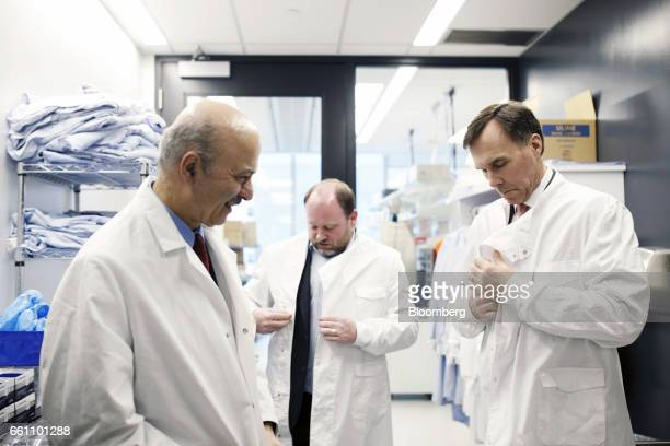 Bill Morneau Canada's finance minister right and Reza Moridi minister of research and innovation of Ontario left put on lab coats during a tour of...