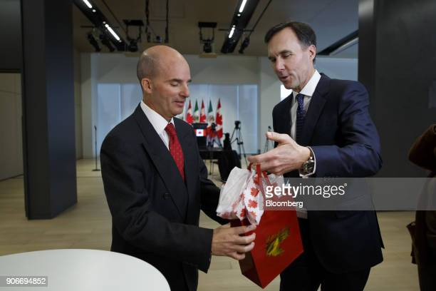 Bill Morneau, Canada's finance minister, right, hands Jose Antonio GonzalezAnaya, Mexico's finance minister, a gift during a joint news conference...