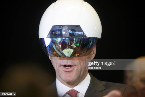 Bill Morneau Canada's finance minister tries on a virtual reality helmet during an artificial intelligence demonstration at the Vector Institute...