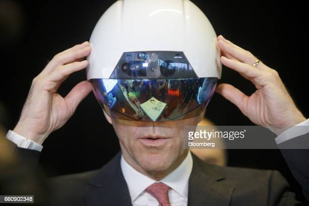 Bill Morneau Canada's finance minister tries on a virtual reality helmet during an artificial intelligence demonstration at the MaRS Discovery...