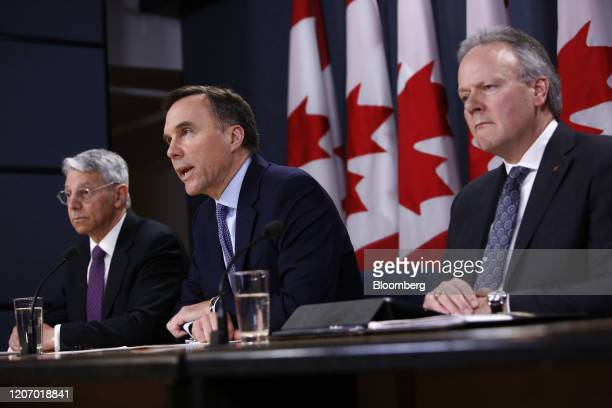 Bill Morneau, Canada's minister of finance, center, speaks while Stephen Poloz, governor of the Bank of Canada, right, and Jeremy Rudin, head of the...