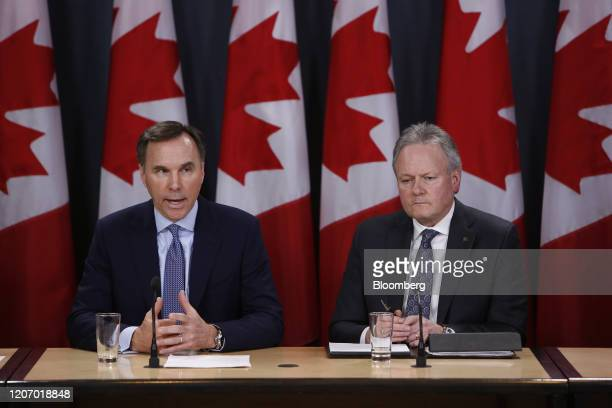 Bill Morneau, Canada's minister of finance, left, speaks while Stephen Poloz, governor of the Bank of Canada, listens during a news conference in...