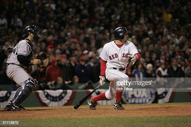 Bill Mueller of the Boston Red Sox hits a game tying single in the ninth inning during game four of the ALCS against the New York Yankees at Fenway...