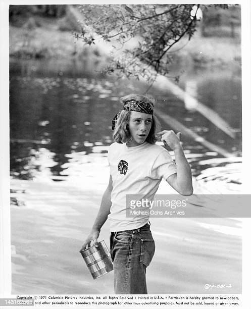 Bill Mumy holding can near water in a scene from the film 'Bless The Beasts And Children' 1971