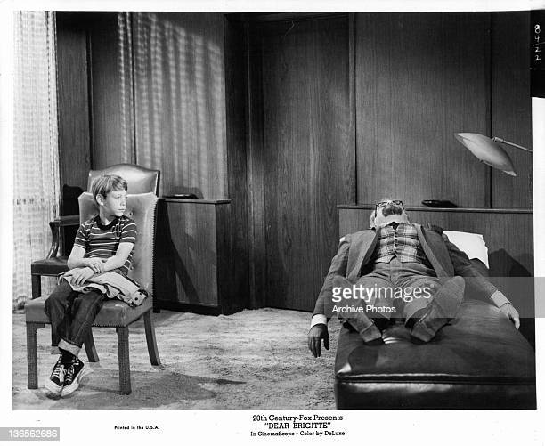 Bill Mumy looking at man lying down in a therapist's chair in a scene from the film 'Dear Brigitte' 1965