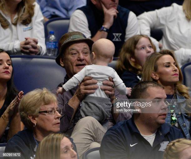 Bill Murray plays with a baby as he watches the game during the NCAA Division I Men's Championship First Round game between the Texas Southern Tigers...