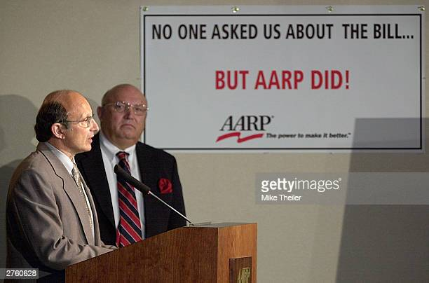 Bill Novelli makes remarks as AARP President Jim Parkel listens at a media conference in reaction to the Medicare vote before Congress November 25...
