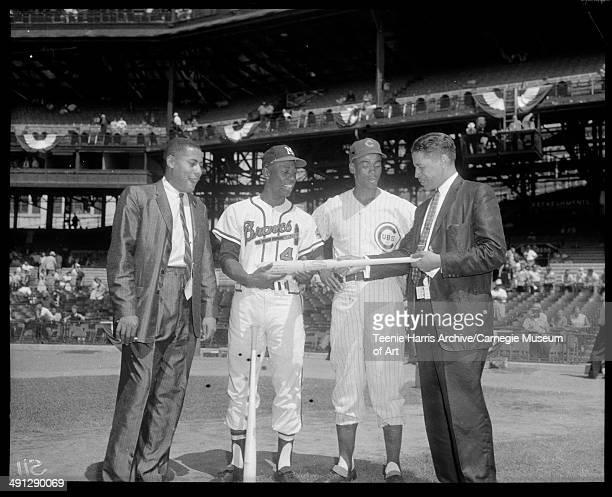 Bill Nunn Jr Chicago Cubs baseball player Ernie Banks Milwaukee Braves player Hank Aaron and Mal Goode examining baseball bat on Forbes Field for...