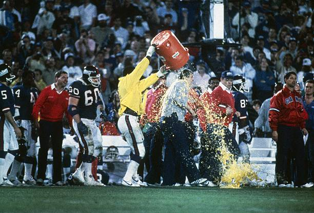Bill Parcells, head coach of the New York Giants is soaked with a bucket of gatorade on the side lines by Harry Carson during Super Bowl XXI on...