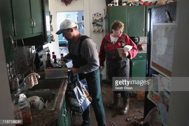 Bill Peeler helps his friend Kathy Drummond remove items from her flooded home on March 20 2019 in Hamburg Iowa Although flood water in the town has...