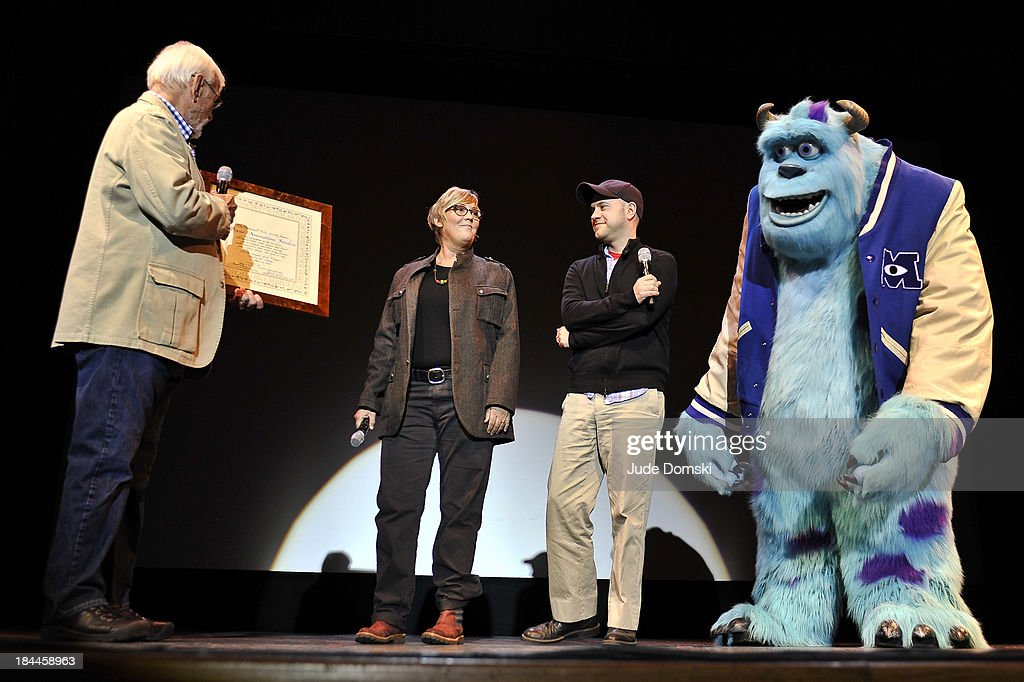 Bill Pence (Director of Film, Hopkins Center for the Arts) presents the Dartmouth Film Award to Producer Kori Rae, Director Dan Scanlon and the Pixar character James P. Sullivan ('Sulley') at a 'A Tribute To Pixar' on October 13, 2013 in Hanover, New Hampshire.
