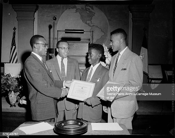 Bill Powell and Mansford Sales presenting certificates of achievement from Greater Pittsburgh Improvement League to 1955 national marbles champion...