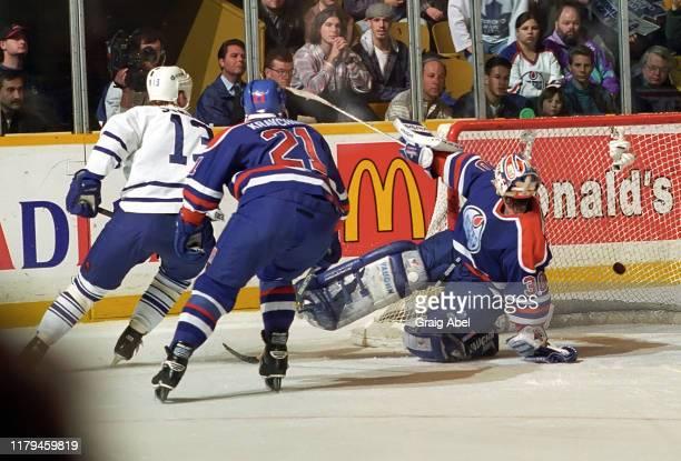 Bill Ranford and Igor Kravchuk of the Edmonton Oilers skate against Mats Sundin of the Toronto Maple Leafs during NHL game action on December 23,...