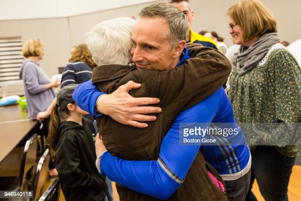 Bill Richard gets a hug after a moment of silence at an event to honor the life of his son Martin Richard a victim killed in the 2013 Boston Marathon...