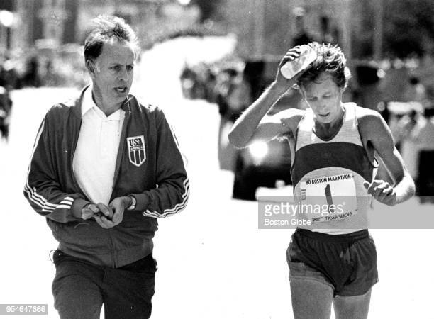 Bill Rodgers right gets some water from his coach Bill Squires left during the Boston Marathon in Wellesley Mass April 21 1980