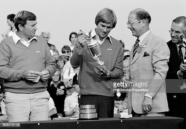 Bill Rogers of the United States receives the trophy from Royal St George's captain Bobby Furber after winning the British Open Golf Championship...
