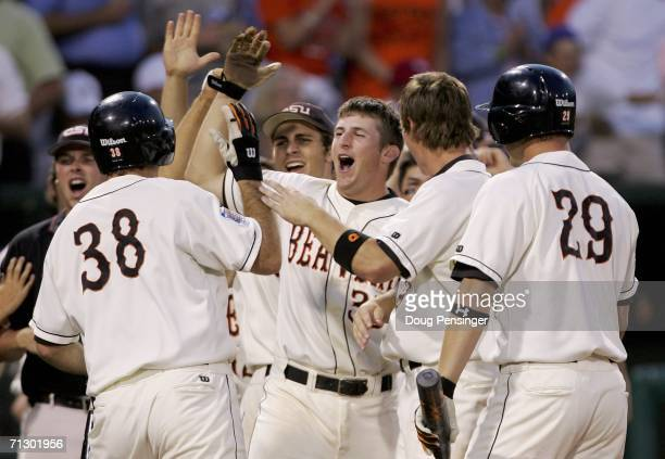 Bill Rowe of the Oregon State Beavers is congratulated by teammates after scoring the winning run after a throwing error by Bryan Steed of the Tar...