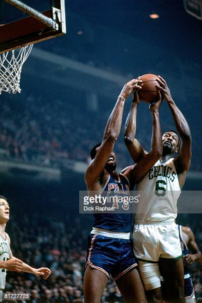 Bill Russell of the Boston Celtics battles for the rebound against Wilt Chamberlain of the Philadelphia 76ers during a game circa 1965 at the Boston...