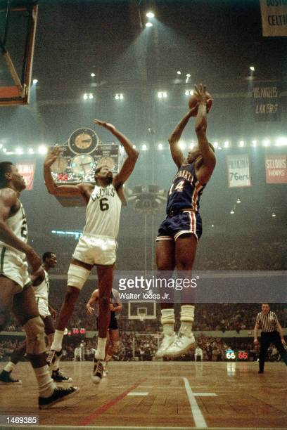 Bill Russell of the Boston Celtics goes for a block against the Cincinnati Royals during the NBA game at the Boston Garden in Boston Massachusetts...