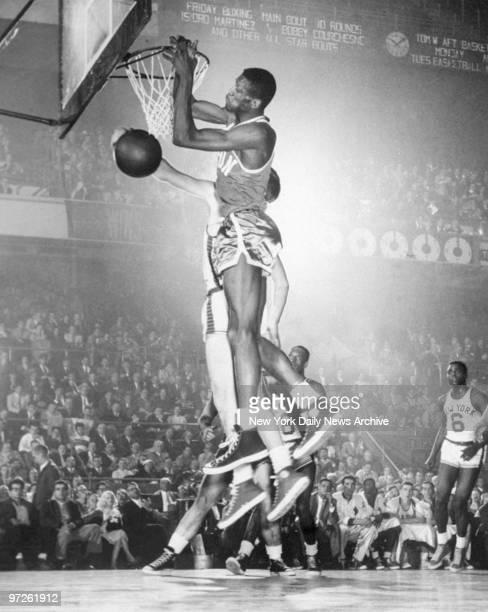 Bill Russell of the Boston Celtics goes rim high for a score against Harry Gallatin of New York in a game won by the Celtics against the Knicks at...