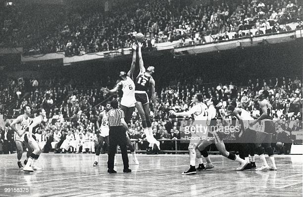 Bill Russell of the Boston Celtics tips off against Gene Wiley of the Los Angeles Lakers during a game in the 196263 season at the Boston Garden in...