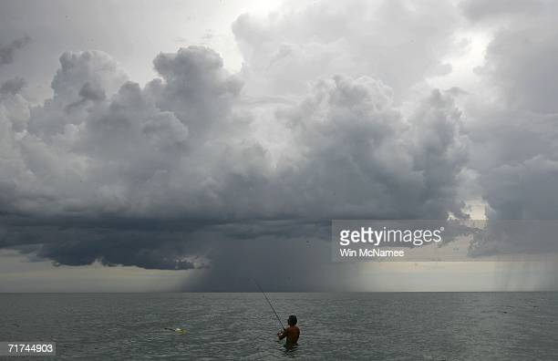 Bill Salter of Boca Raton fishes in the ocean as storm clouds from Tropical Storm Ernesto approach from the south August 29 2006 off Captiva Island...