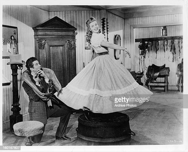 Bill Shirley plays a flute as Eileen Christy twirls in a scene from the film 'I Dream Of Jeanie' 1952