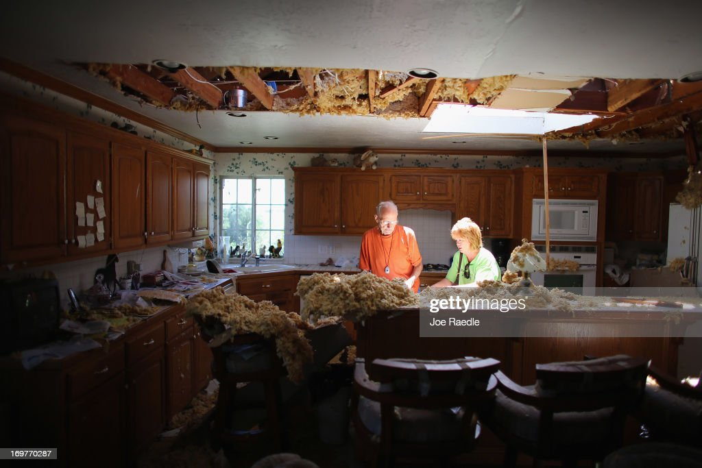Bill Thesing (L), who was injured in his home when a tornado hit, returned to what was left of it from the hospital to salvage items as his friend Tammy Hicks helps on June 1, 2013 in El Reno, Oklahoma. The tornado ripped through the area killing at least nine people, injuring many others and destroying homes and buildings.
