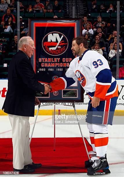 Bill Torrey shakes hands with Doug Weight of the New York Islanders during a tribute honoring Bill Torrey as the Florida Panthers play host to the...