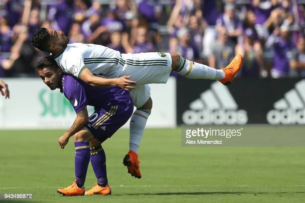 Bill Tuiloma of Portland Timbers falls onto Yoshimar Yotun of Orlando City SC after a challenge during an MLS soccer match at Orlando City Stadium on...