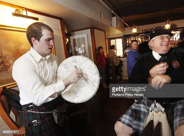 Bill Whalen left of Livermore and Kip McClure of Belgrade Lakes take turns playing a bodhran an Irish drum at Ri Ra Irish Pub and Restaurant in...