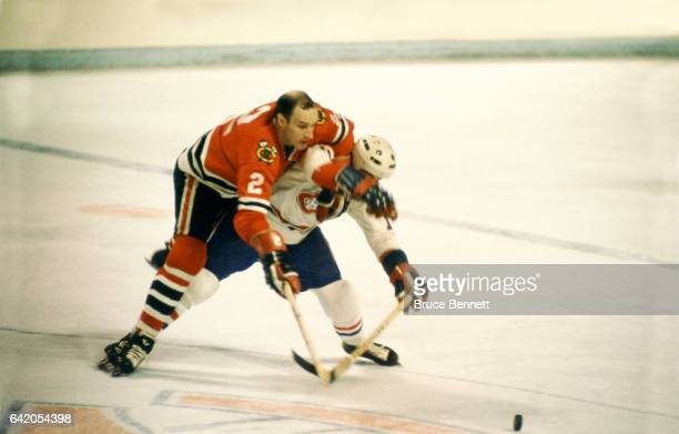 Bill White of the Chicago Blackhawks defends against an unidentified Montreal Canadiens player circa 1974 at the Montreal Forum in Montreal Quebec...