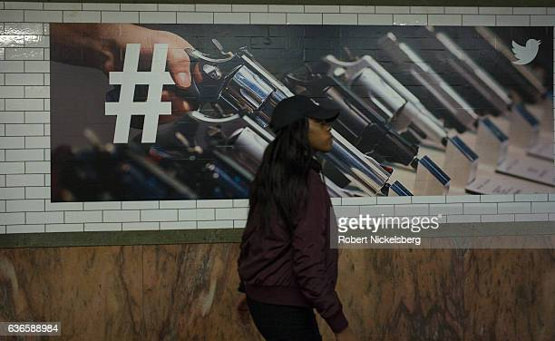 A billboard advertisement for Twitter using pistols hangs from a wall December 9 2016 in a subway station in New York City