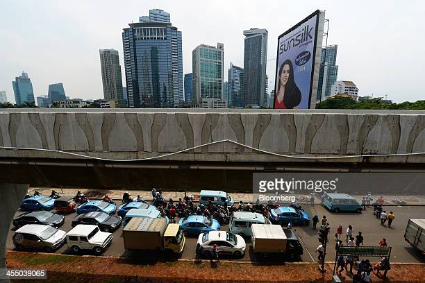 A billboard advertisement for Unilever's Sunsilk brand stands roadside as vehicles sit in traffic in Jakarta Indonesia on Tuesday Dec 10 2013...