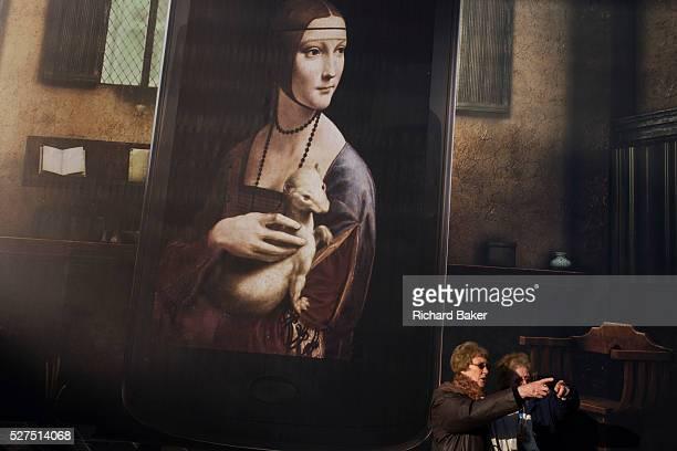 Billboard advertising Leonardo da Vinci's Portrait of Cecilia Gallerani above London tourists at National Gallery The da Vinci portrait is identified...
