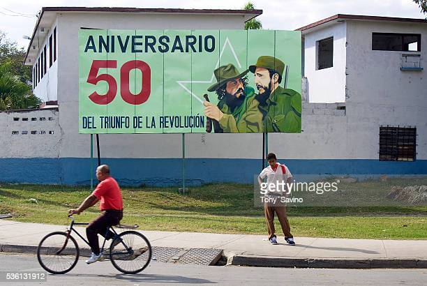 A billboard bearing the image of Fidel Castro and Camillo Cienfuegos describing the triumph of the 50 year anniversary of the revolution at a bus...