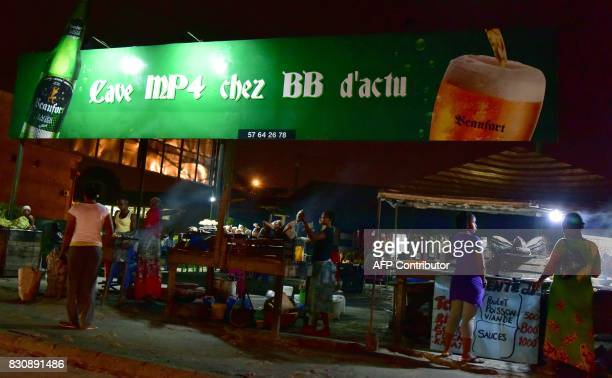 Billboard displaying an advertisement for Ivoire lager beer is seen near a bar in Abidjan on July 13, 2017. On posters and huge billboards around the...
