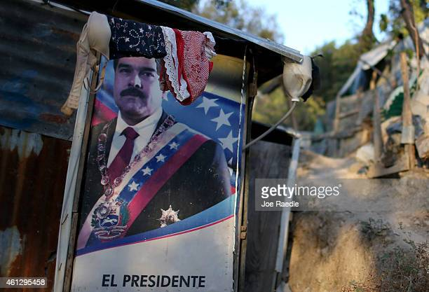 A billboard featuring Venezuelan President Nicolas Maduro is used as a wall for a home made out of tin and tarps that is built over the land where a...