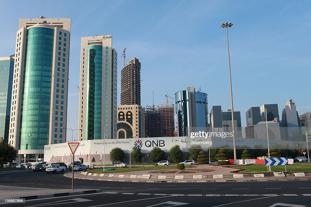 A billboard for the Qatar National Bank SAQ (QNB) branch stands on a highway near office high rises and new buildings under construction in Doha, Qatar, on Thursday, Nov. 22, 2012. Qatar Telecom QSC, the country's biggest company by revenue, is seeking a syndicated loan for about $1 billion to refinance existing debt, according to a person with direct knowledge of the deal. Photographer: Gabriela Maj/Bloomberg via Getty Images