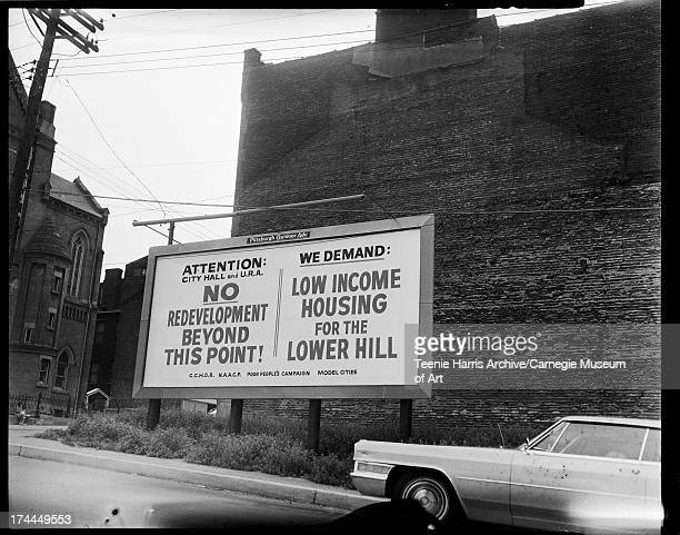 Billboard inscribed 'Attention City Hall and URA No Redevelopment Beyond This Point We Demand Low Income Housing for the Lower Hill CCHDR NAACP Poor...